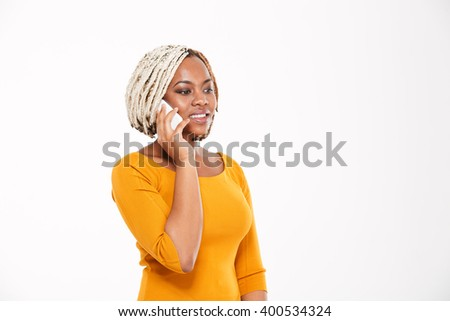 Pretty smiling young african american woman talking on mobile phone over white background - stock photo