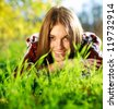 Pretty smiling young girl lying on green grass close up,in summer park. - stock photo