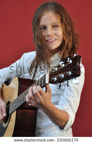 Pretty smiling young teen girl playing acoustic guitar in the street.  - stock photo