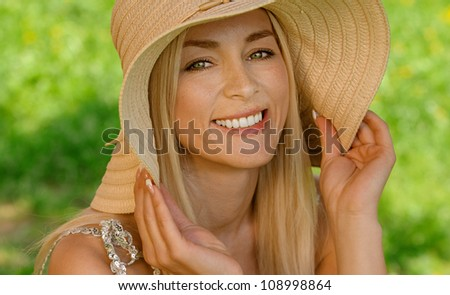 Pretty smiling young woman in hat sitting on wooden bench, against green of summer park.