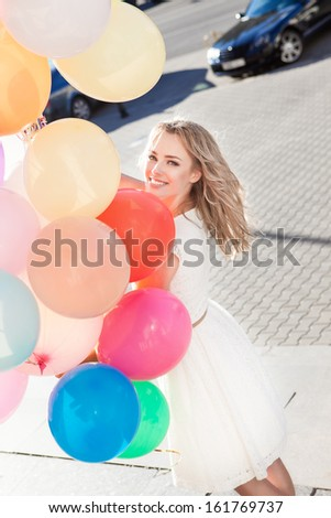 pretty smiling young woman in white summer dress with a bunch of multicolored balloons on sunny day in city