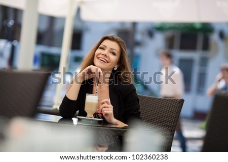 pretty smiling young woman sitting in the cafe with a cup of coffee - stock photo