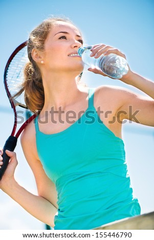Pretty sportswoman with racket on shoulders at the tennis court