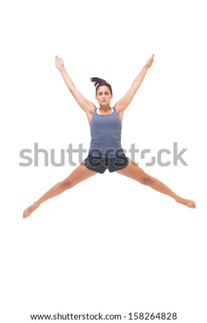 Pretty sporty brunette jumping in the air on white background