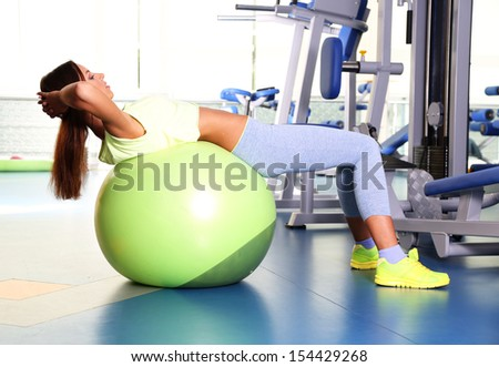 Pretty sporty girl do physical exercises on fit-ball in gum - stock photo