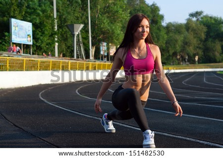 Pretty sporty strong slim and fit young woman athlete doing stretching exercises, standing on low start, looking forward and smiling. At the stadium, on running tracks - stock photo