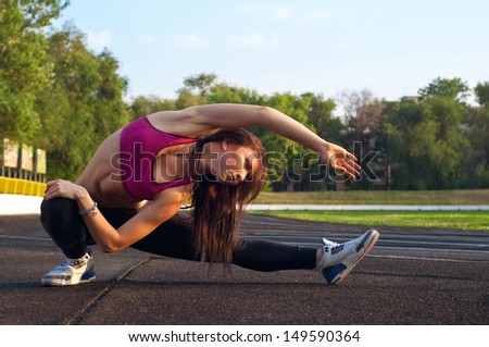 Pretty sporty strong slim and fit young woman sitting, doing split and stretching exercises, stretching out to reach her foot. At stadium, on running tracks. During sunset. Green trees at background - stock photo