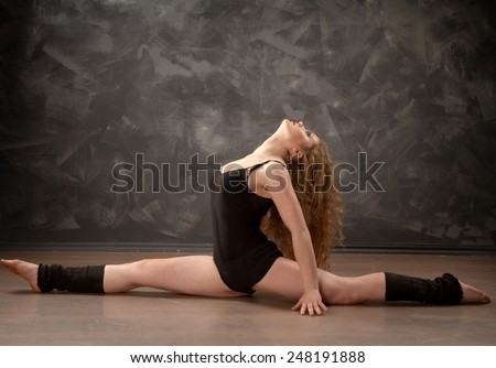 Pretty sporty strong slim and fit young woman sitting, doing split and stretching exercises, sitting on a full split. woman engaged in fitness and dance studio - stock photo
