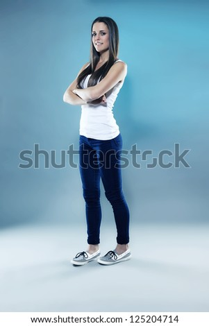 pretty sporty teenager with crossed arms in blue light - stock photo