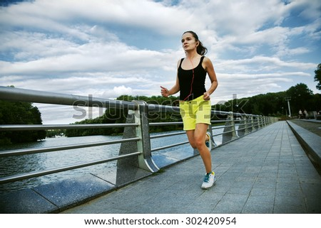 Pretty sporty woman jogging at park
