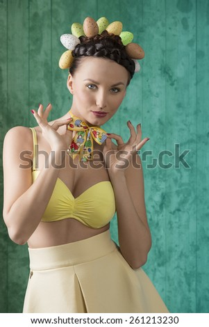 Pretty, spring, fresh woman in yellow dress, top and funny loop on her neck. She have funny hairstyle with easter eggs. - stock photo