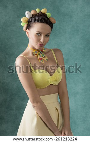 Pretty, spring woman with brown hairstyle with eggs, wearing loop on the neck and yellow top and dress.  - stock photo