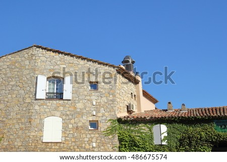 Pretty stone Provencal cottage with copy space and bright blue sky, with traditional shutters