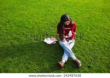 Pretty student girl sitting on the grass reading a book outdoors, young woman sitting on grass and read a book - stock photo