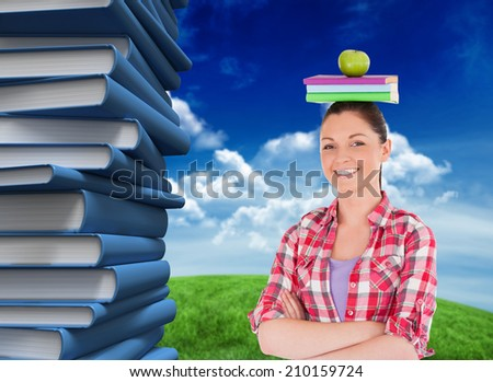 Pretty student holding an apple and books on her head against green field under blue sky - stock photo