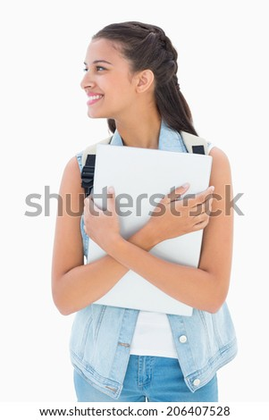 Pretty student holding her laptop on white background - stock photo