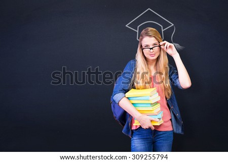 Pretty student in the library against navy blue - stock photo