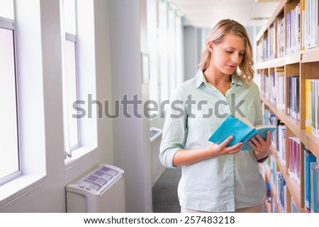 Pretty student in the library at the university - stock photo