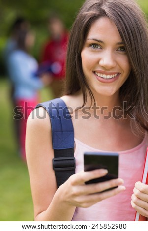 Pretty student sending a text outside on campus at the university - stock photo