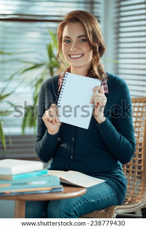 Pretty student showing a blank notebook - stock photo