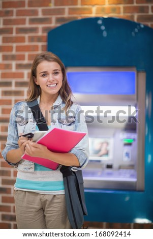 Pretty student standing smiling at camera at the atm in college - stock photo