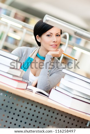 Pretty student studies with piles of books sitting at the table at the reading hall
