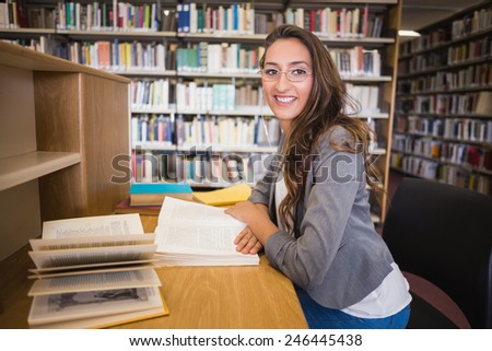 Pretty student studying in the library at the university - stock photo