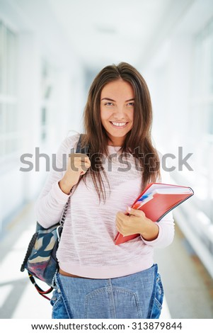 Pretty student with backpack and books looking at camera