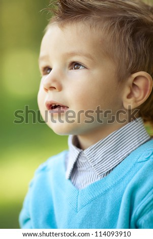 Pretty stylish baby boy looking up in the park. Close up. Outdoor shot. - stock photo