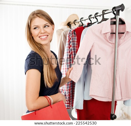 Pretty stylish female buyer choosing casual clothes in the shop. Young attractive Caucasian woman model holding colorful shopping bags. - stock photo