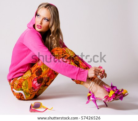 Pretty stylish woman in colorful clothing on gray background