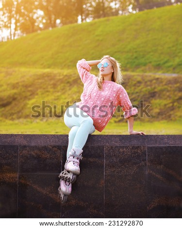 Pretty stylish woman in sunglasses with roller skates posing in the city park - fashion, extreme, youth and people concept  - stock photo