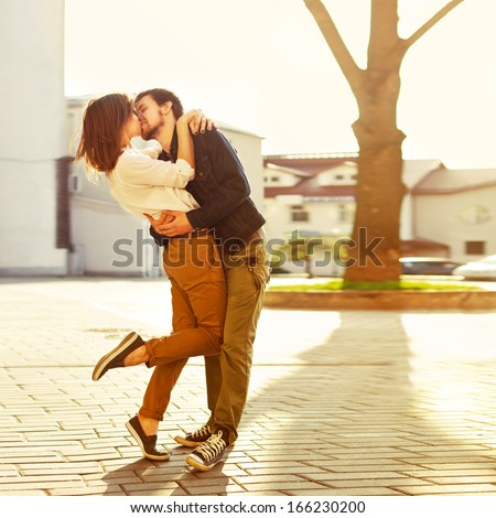 Pretty summer sunny outdoor portrait of young stylish couple while kissing on the street. - stock photo