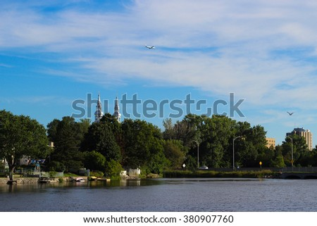 Pretty summer view of embankment, church and airplane, Montreal - stock photo
