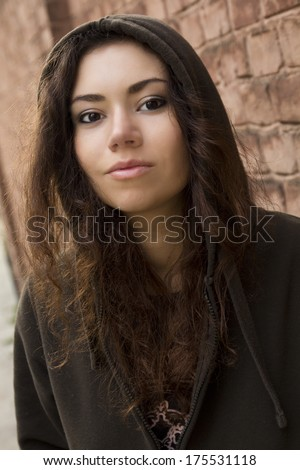 Pretty sun-tanned Hispanic teenager girl with fluffy curly dark hair in brown hood near the brick wall outdoor