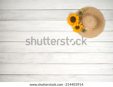 Pretty Sunflowers Picked from Garden on a Ladies Sunhat from above on texture rustic white or gray board background with blank or empty room or space for copy, text, your words.  Horizontal  - stock photo
