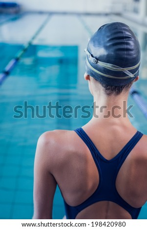 Pretty swimmer standing by the pool at the leisure center - stock photo