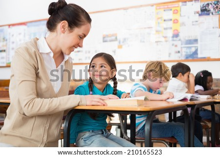 Pretty teacher helping pupil in classroom at the elementary school
