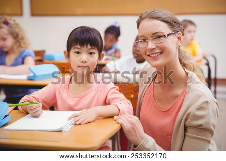Pretty teacher helping pupil in classroom smiling at camera at the elementary school - stock photo