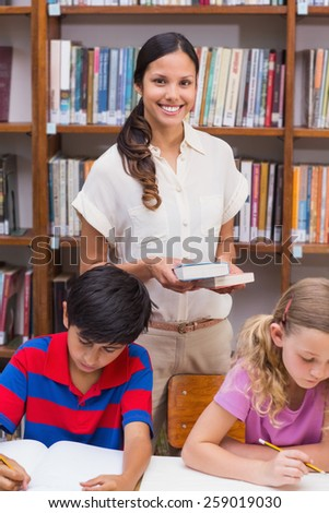 Pretty teacher helping pupils in library at the elementary school - stock photo