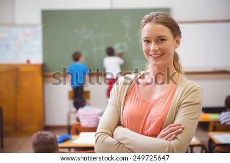 Pretty teacher smiling at camera at back of classroom at the elementary school