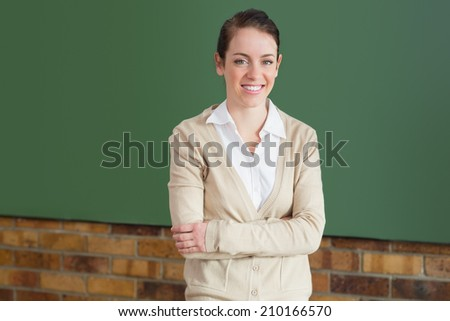 Pretty teacher smiling at camera at top of classroom at the elementary school