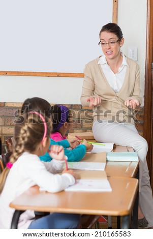 Pretty teacher talking to the young pupils in classroom at the elementary school