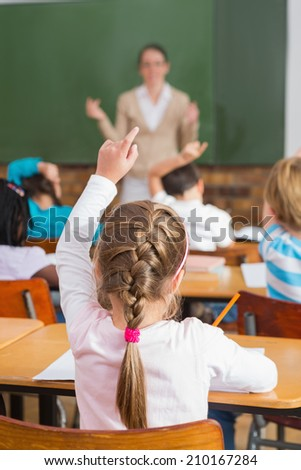 Pretty teacher talking to the young pupils in classroom at the elementary school - stock photo