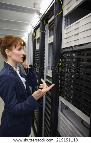 Pretty technician talking on phone while looking at server in large data center