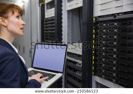 Pretty technician using laptop while working on servers in large data center