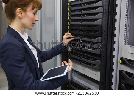 Pretty technician using tablet pc while working on servers in large data center