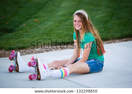 Pretty teen girl in roller skates smiling as she sits on the sidewalk - stock photo