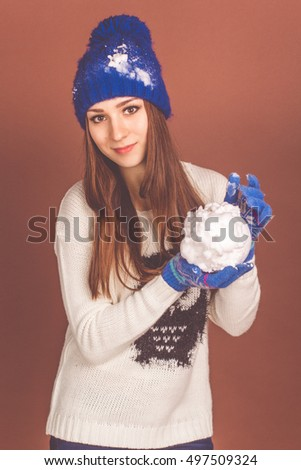 Pretty teen girl is holding artificial snowball