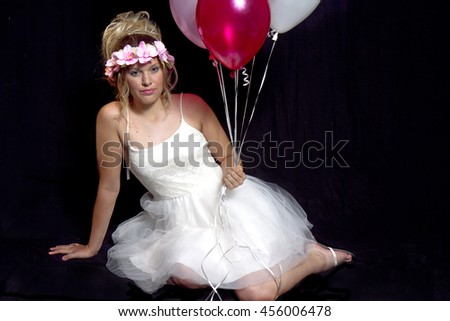 Pretty teen girl isolated on black background holding onto balloons.  Floral wreath on her head along with wearing delicate white tulle party dress